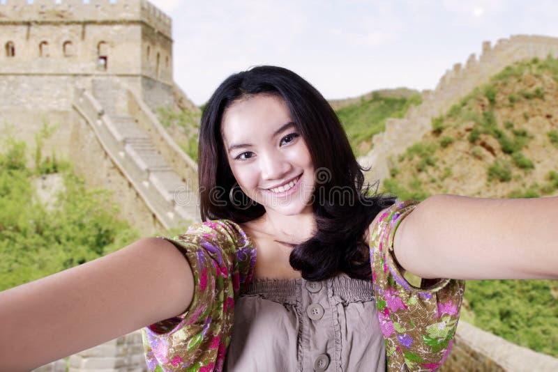 拍照片的十几岁的女孩在长城 免版税库存照片
