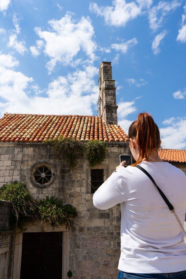 拍照片的女孩对一个老教会在布德瓦,有智能手机的黑山在有房子和木头的石门面的老镇 免版税库存图片
