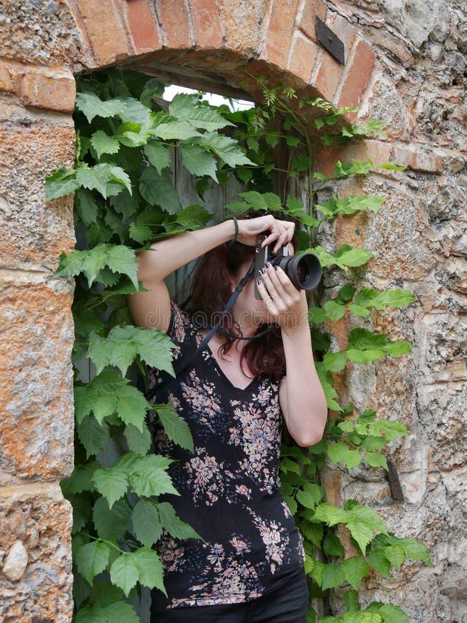 拍照片的女孩摄影师,使用葡萄酒照相机 免版税库存照片