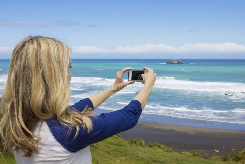 拍照片的妇女在与她的智能手机的海滩 库存照片