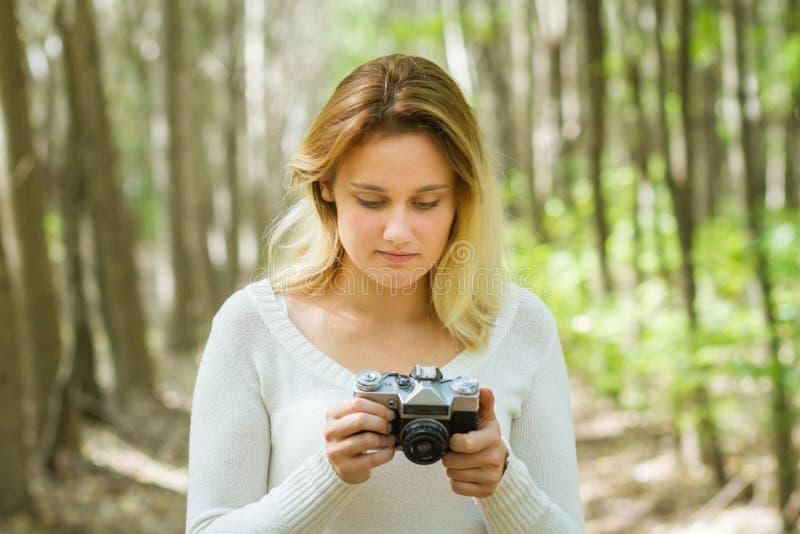 拍照片的妇女在森林里 免版税库存照片