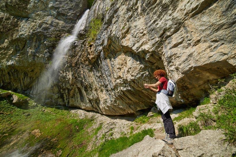 拍照片的妇女在瀑布附近 库存图片