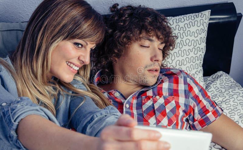 拍照片的妇女对睡觉在床上的人 免版税库存照片