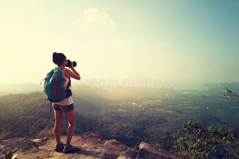 拍照片的妇女摄影师在山峰 库存图片