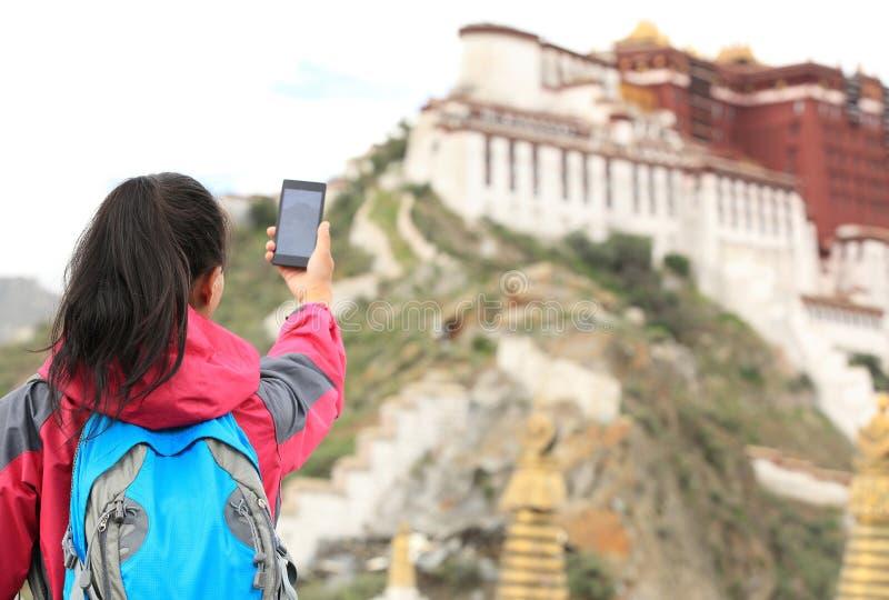 拍照片的妇女用途巧妙的电话在西藏 免版税库存照片