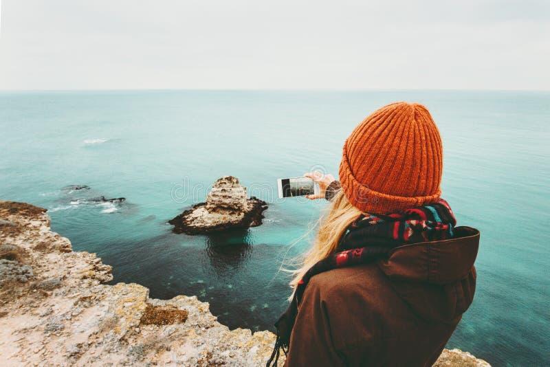 拍照片的妇女由海风景智能手机  库存图片