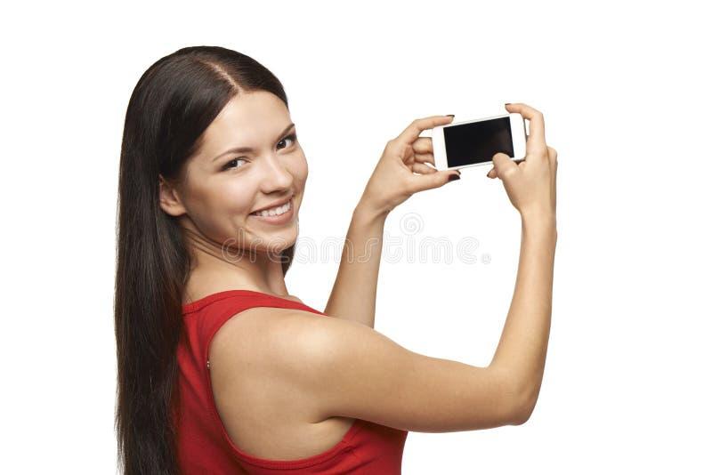 拍照片的妇女通过手机 库存图片