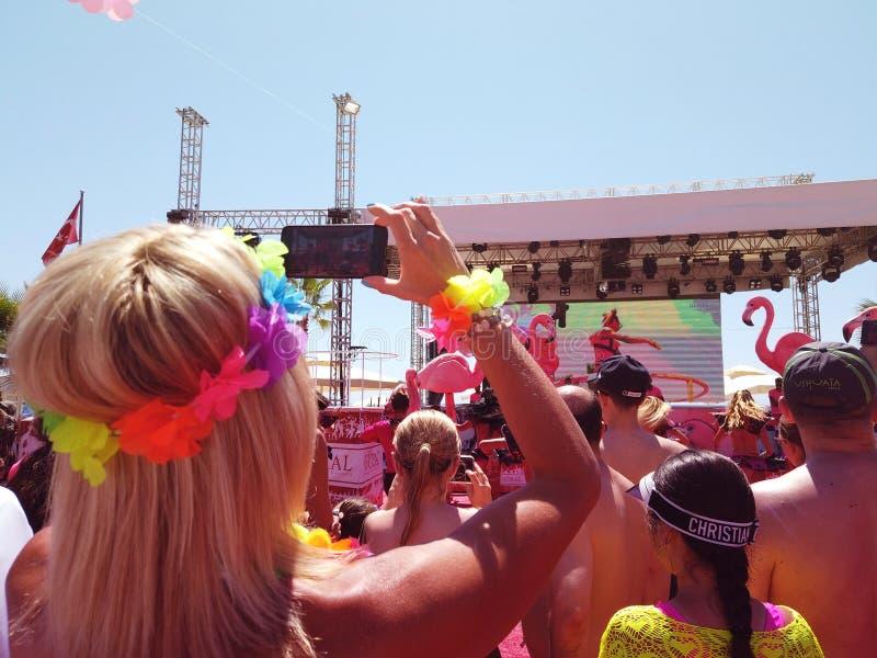 拍照片的室外音乐节的年轻女人使用手机 免版税库存照片
