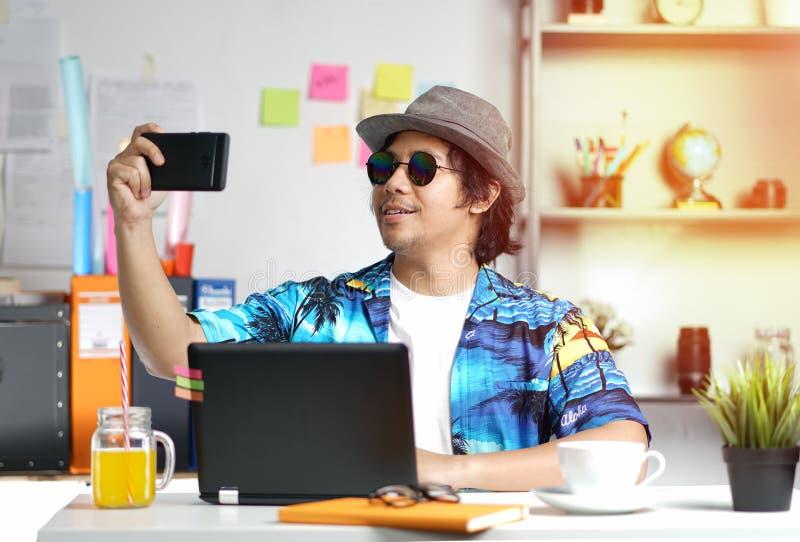 拍照片的时髦的年轻人,当研究夏天Vacatio时 图库摄影