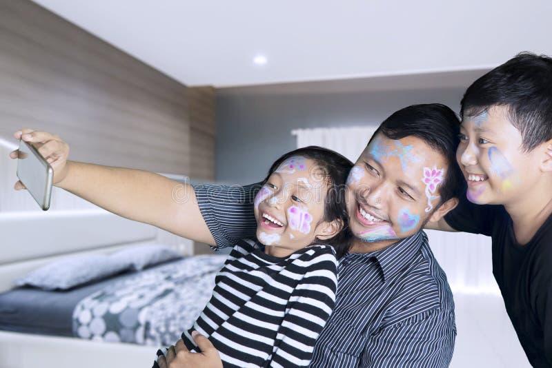 拍照片的父亲和孩子在卧室 免版税库存照片