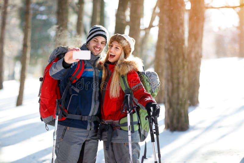 拍照片的男性和女性远足者在木头的冬天 库存照片