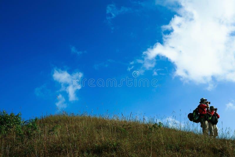 拍照片的男性游人在小山的上面附近 库存图片