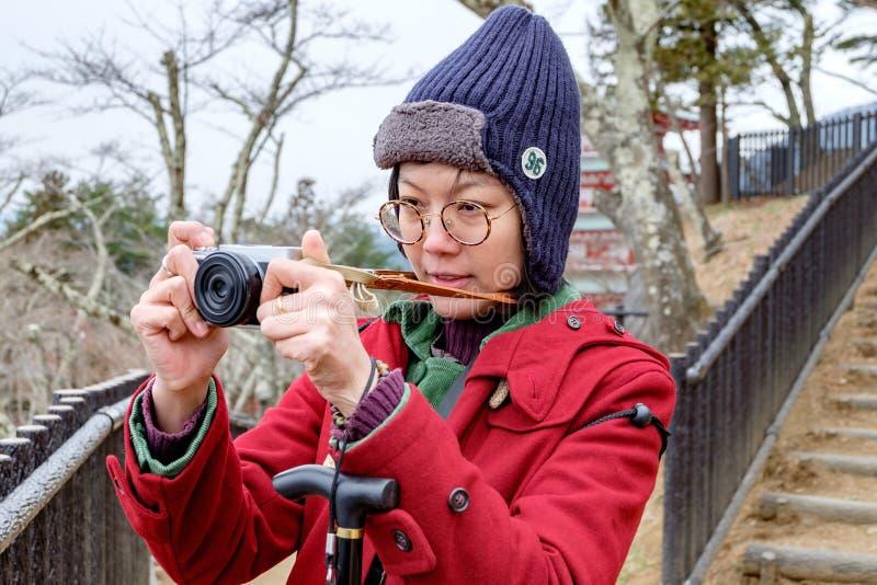拍照片的红色外套的妇女在日本庭院 免版税库存照片