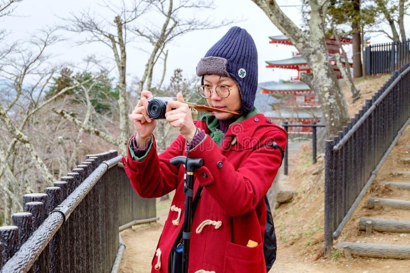 拍照片的红色外套的妇女在日本庭院 免版税库存图片