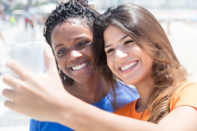 拍照片的非裔美国人和白种人女孩 免版税图库摄影