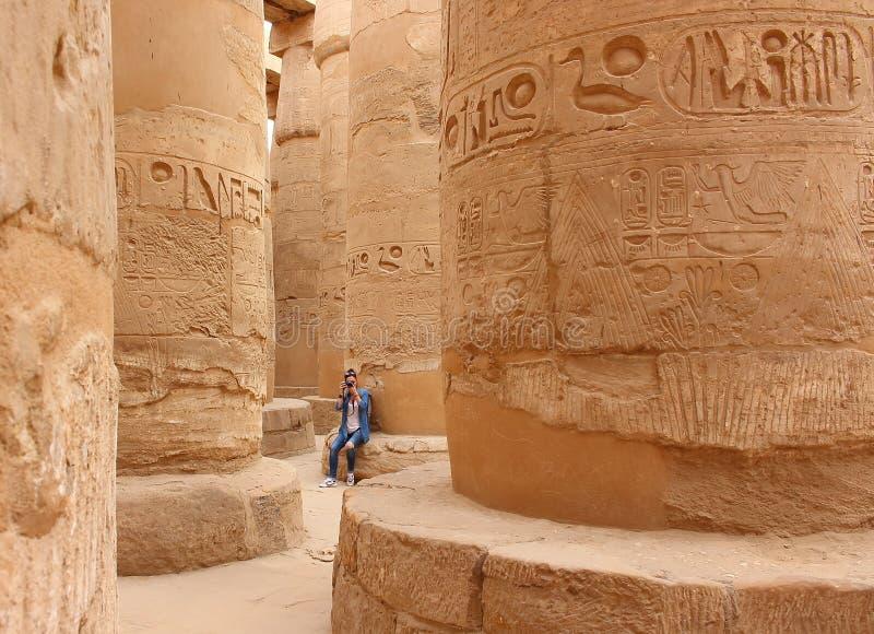 拍照片的年轻美丽的妇女在卡纳克神庙的寺庙次附尖大厅之间的专栏在卢克索,埃及 免版税库存照片