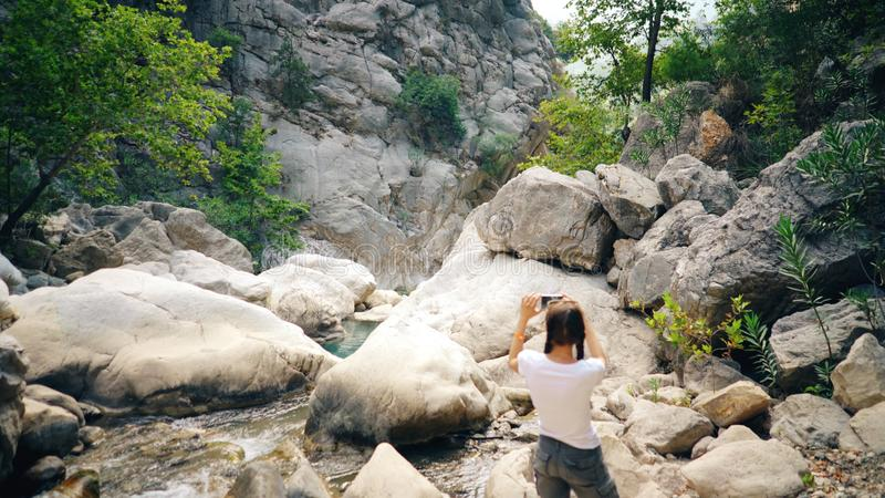 拍美丽的峡谷的照片在她的智能手机照相机的年轻旅游妇女在旅行期间 库存照片