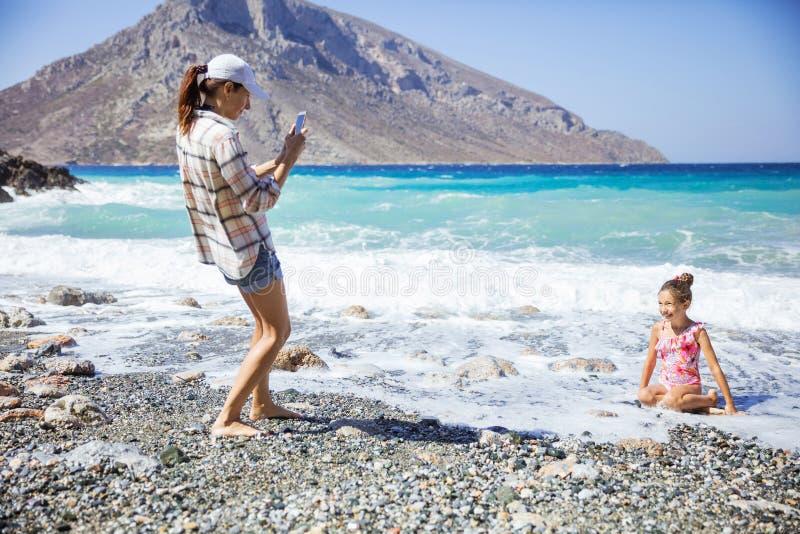 拍美丽的年轻女儿的照片海滩的白种人母亲 库存照片