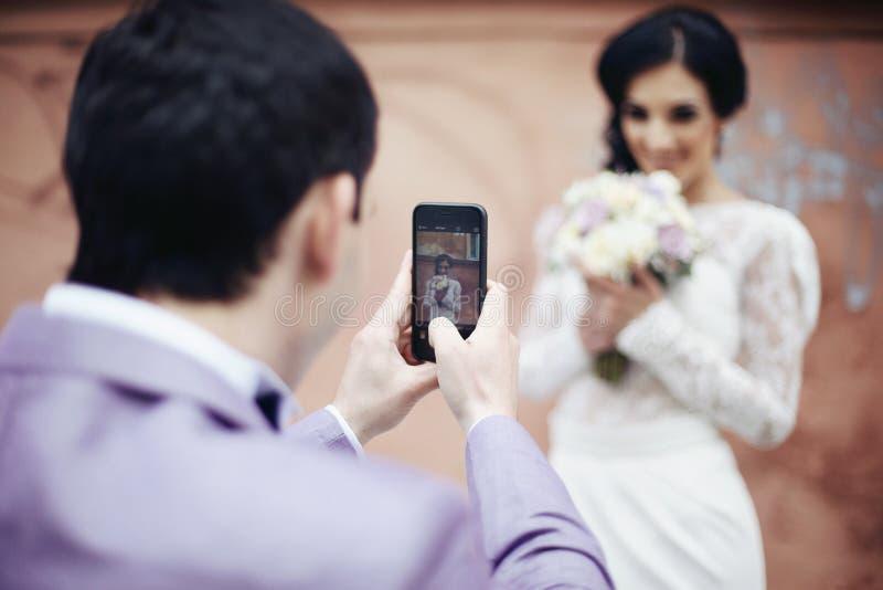 拍美丽的新娘的照片他的电话的英俊的新郎 库存照片