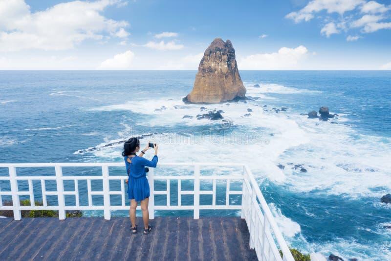 拍美好的海景的照片年轻女人 免版税库存照片