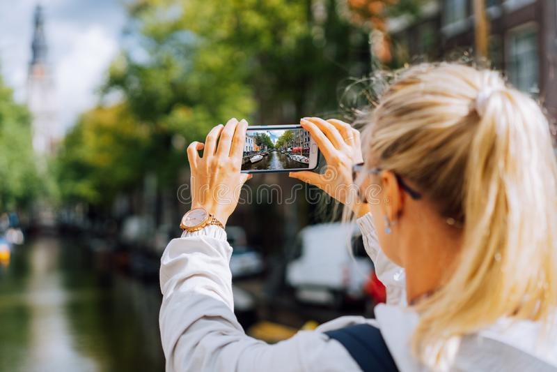 拍运河的照片妇女游人在手机的阿姆斯特丹 温暖的金子下午阳光 旅行在欧洲 免版税图库摄影