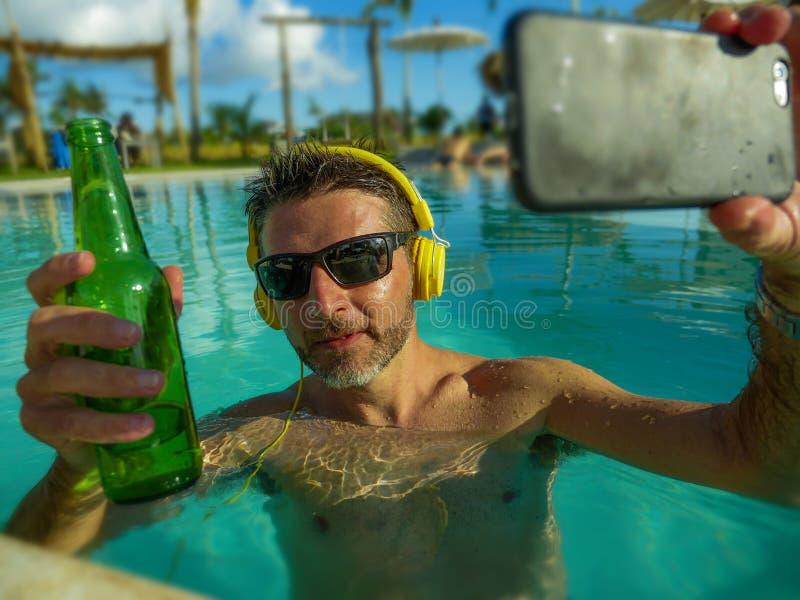 拍selfie照片用手机饮用的啤酒和听到音乐的年轻愉快和可爱的人在热带手段 免版税库存照片