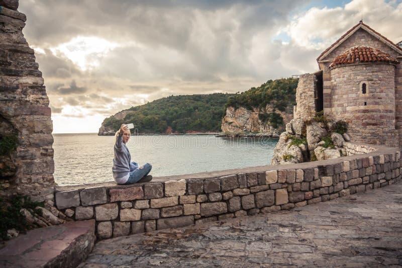 拍selfie照片的妇女旅客在日落期间坐有海的石墙和在背景的剧烈的天空在老欧洲镇 免版税库存照片