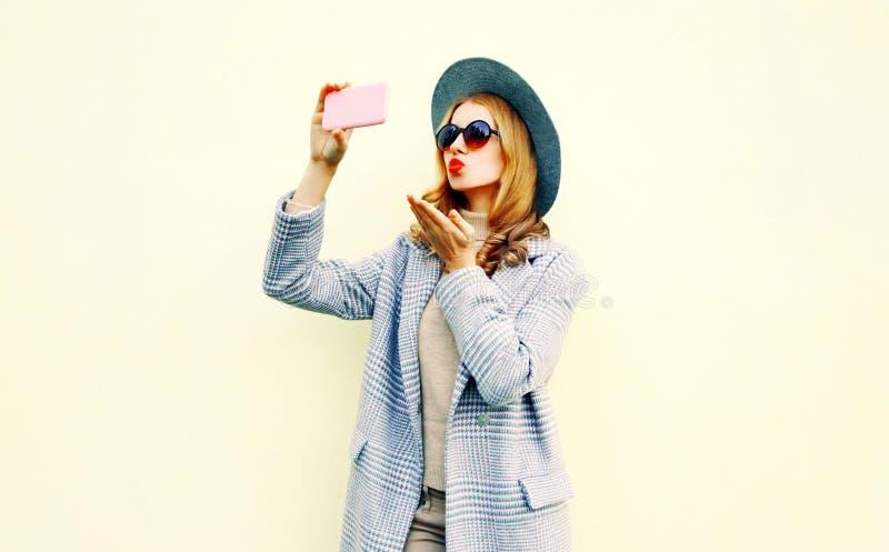 拍selfie照片的年轻女人由吹红色嘴唇的智能手机送在桃红色外套夹克,圆的帽子的甜空气亲吻 库存图片