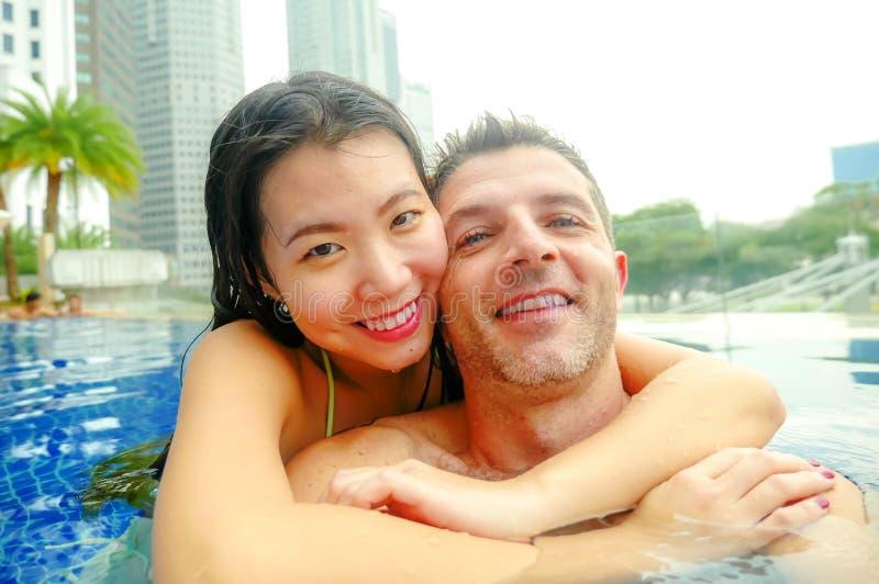拍selfie照片的年轻愉快和有吸引力的嬉戏的夫妇与手机一起在豪华都市旅馆无限水池enj 免版税图库摄影