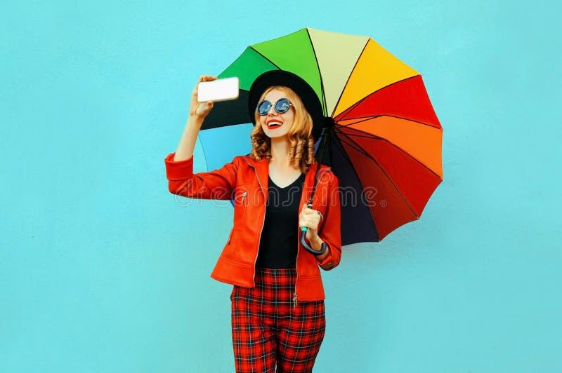 拍selfie照片的愉快的微笑的妇女由有五颜六色的伞的电话在红色夹克,在蓝色墙壁上的黑帽会议 图库摄影