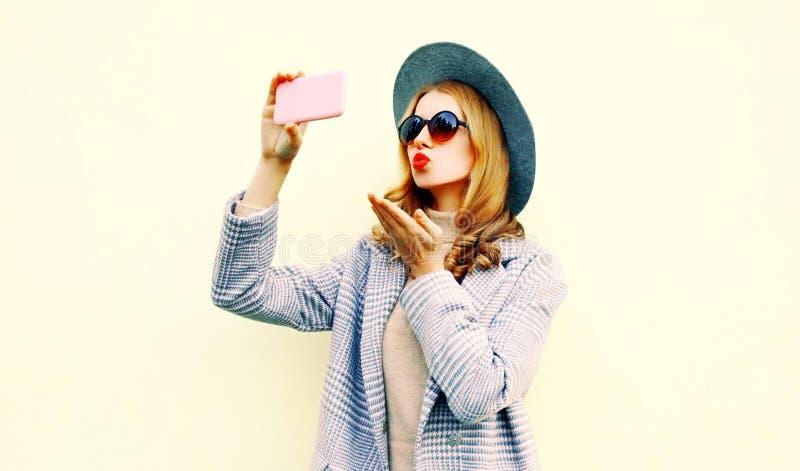 拍selfie照片的美女由吹红色嘴唇的智能手机送在桃红色外套夹克,圆的帽子的甜空气亲吻 免版税库存图片