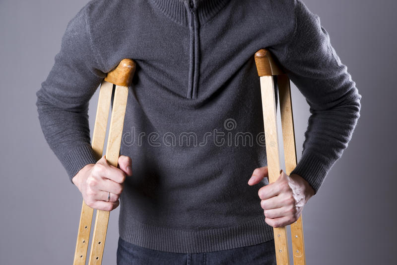 拐杖的人在灰色背景 免版税库存图片