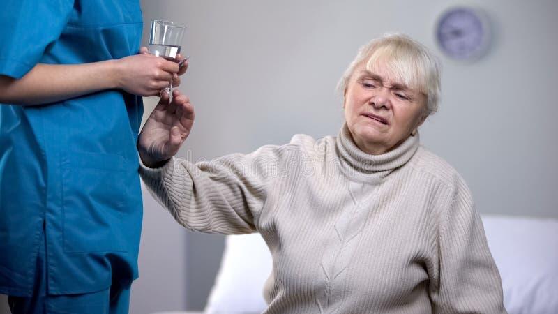 拒绝从护士的老妇人疗程在康复中心,治疗 库存图片