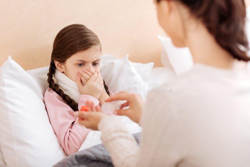 拒绝害怕的孩子采取她药片 免版税库存照片