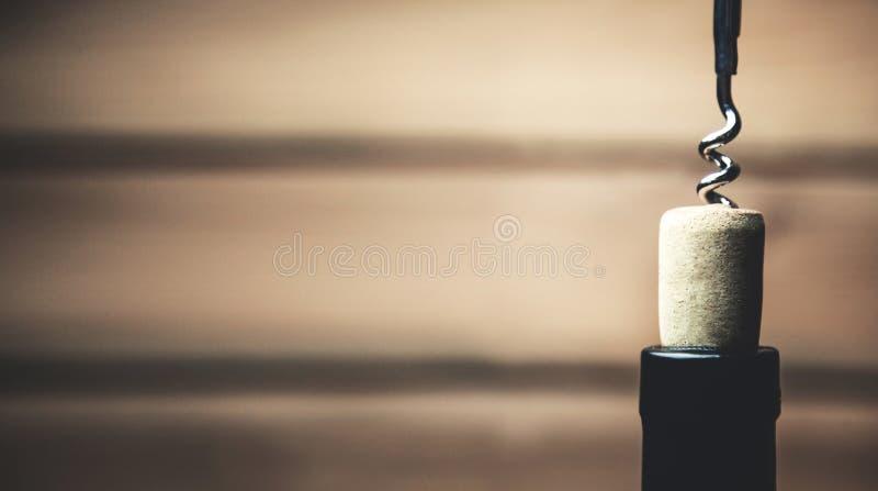 拔塞螺旋和瓶在木背景的酒 免版税图库摄影