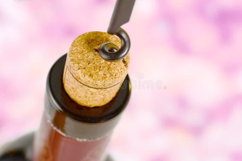 拔塞螺旋拔出从瓶的黄柏红酒 宏指令的黄柏关闭,在桃红色背景 库存图片