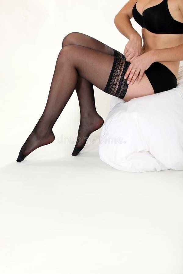 拔她的长袜的妇女 免版税库存照片