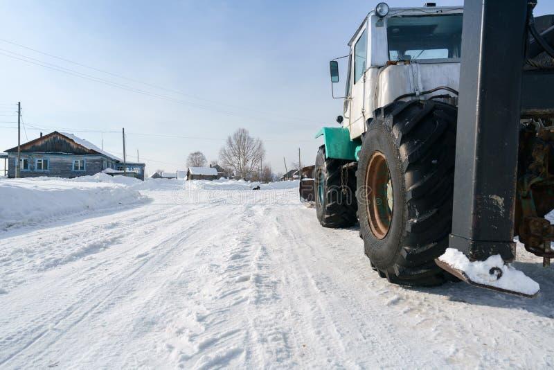 拖拉机乘驾通过村庄在冬天 免版税库存照片