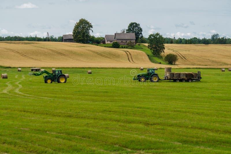 拖拉机从另一台拖拉机装载大包在拖车上的干草 库存图片