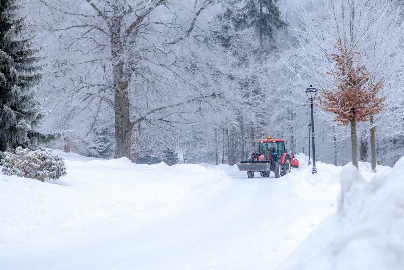 拖拉机从雪清洗路在冬天 库存图片