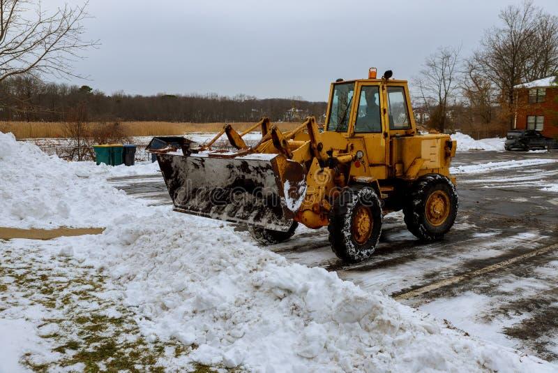 拖拉机在城市街道的清洁雪和在降雪以后的一个停车场 图库摄影