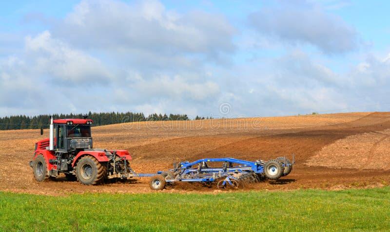 拖拉机在村庄耙松地面 免版税库存图片