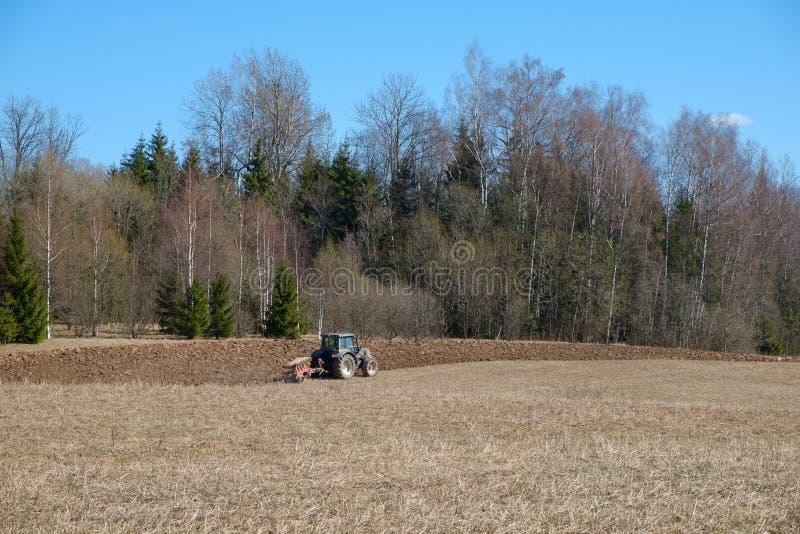 拖拉机在森林附近犁地球 图库摄影