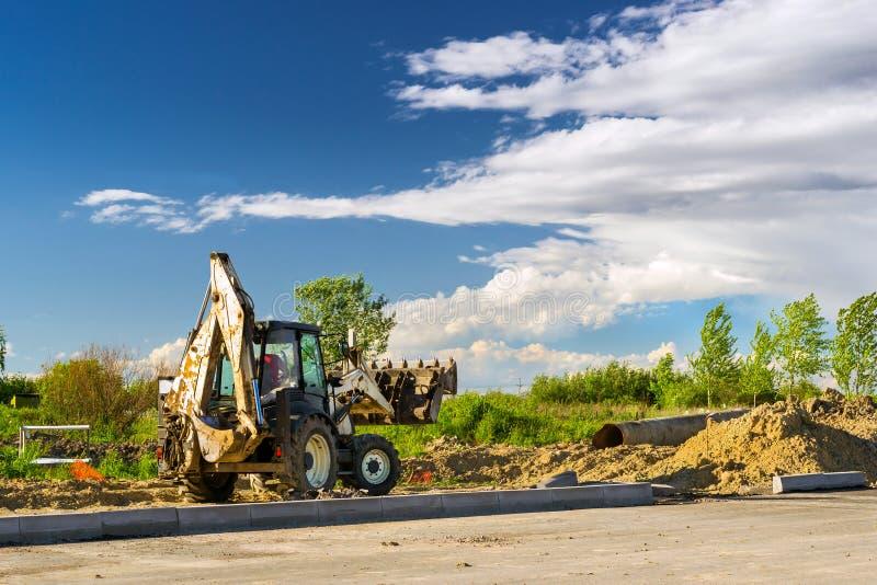 拖拉机挖掘工作,建筑速度路 免版税图库摄影