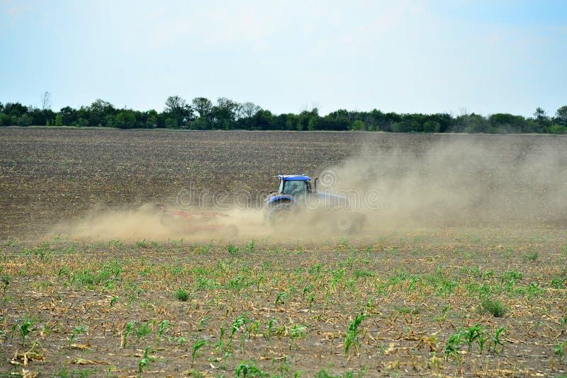 拖拉机犁地球,并且尘土飞行用不同的方向,土地为播种在oen做准备 免版税库存照片