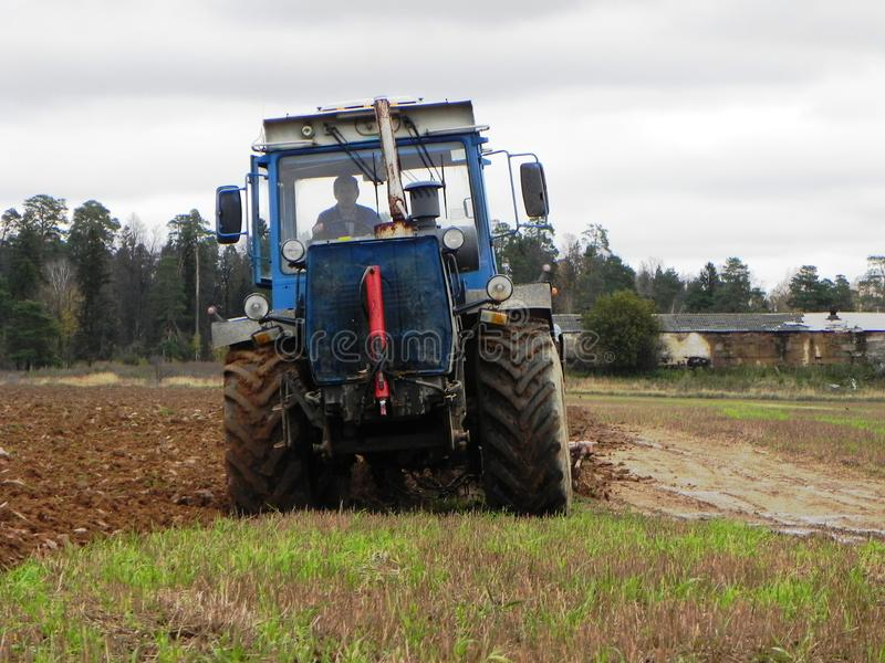 拖拉机犁领域 拖拉机在领域乘坐并且犁耕地 r 库存图片