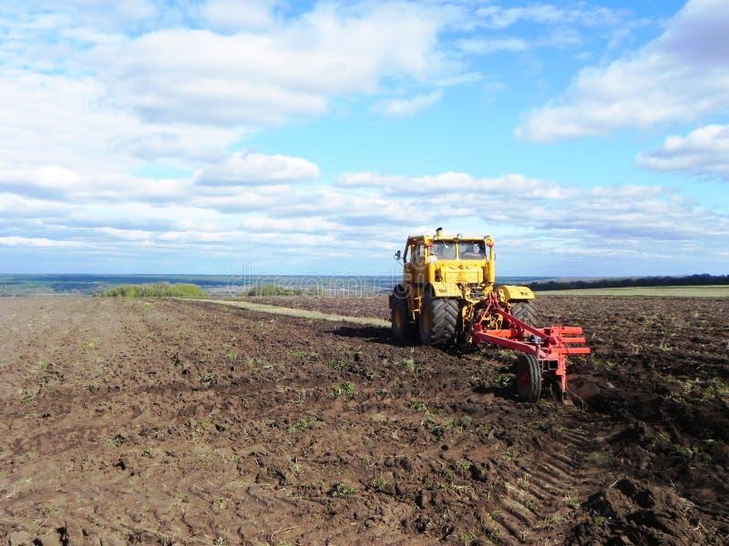 拖拉机犁领域 拖拉机在领域乘坐并且犁耕地 r 免版税库存图片