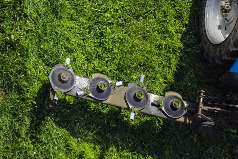 拖拉机的登上的圆盘刈草机在农业劳动期间,在迅速自转时割水多的绿色草坪草 库存照片