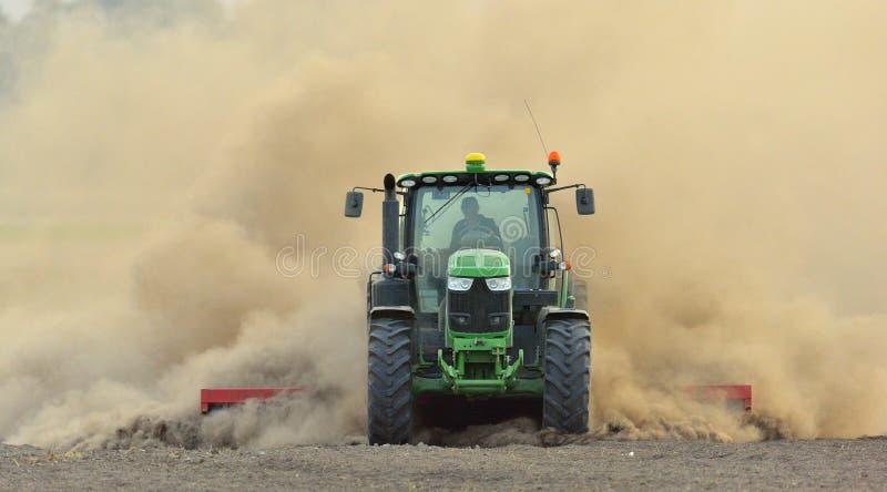 拖拉机耙松在巨大的尘云的领域 免版税库存照片