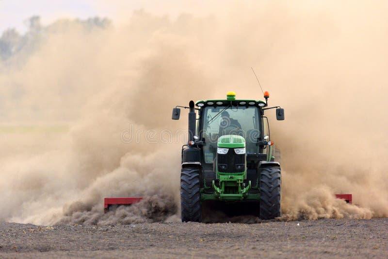拖拉机耙松在巨大的尘云的领域 免版税库存图片